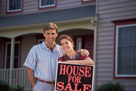 Couple with a home for sale sign